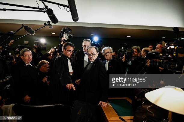 Lyon archbishop cardinal Philippe Barbarin flanked by lawyers and surrounded by journalists looks on as he arrives in Lyon court to attend his trial...