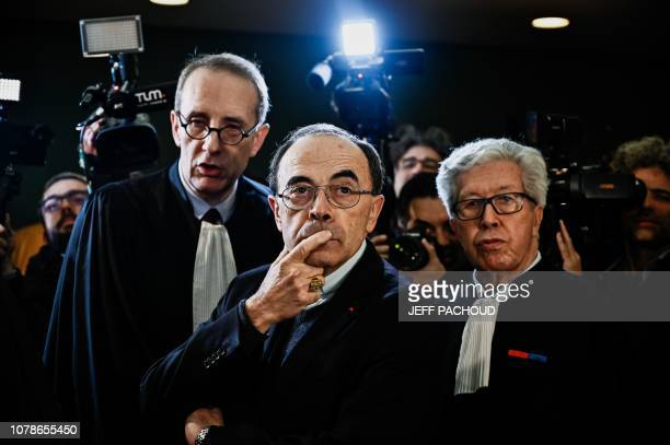 TOPSHOT Lyon archbishop cardinal Philippe Barbarin flanked by lawyers gestures as he arrives in Lyon court to attend his trial on January 7 charged...