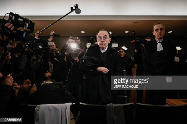 Lyon archbishop cardinal Philippe Barbarin surrounded by journalists looks on as he arrives in Lyon court to attend his trial on January 7 charged...
