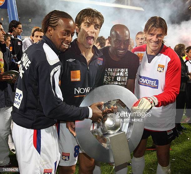 Lyon players French forward Sidney Govou Brazilian midfielder Juninho Brazilian defender Claudio Cacapa and French goalkeeper Gregory Coupet pose...