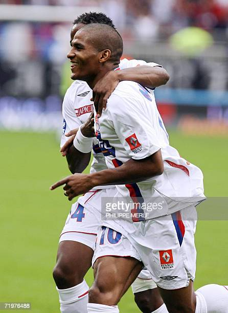 Lyon's French midfielder Florent Malouda celebrates with his teammate Sidney Govou after he scored a goal during the French L1 football match Lyon vs...