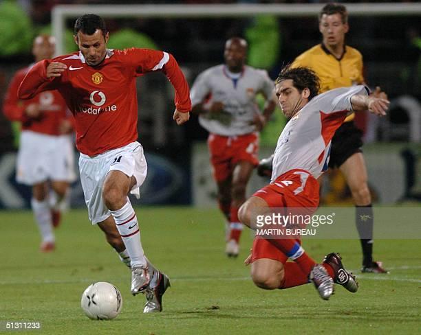 Manchester United's forward Welsh Ryan Giggs is tackled by Lyon's midfielder Brazilian Pernambucano Juninho, 15 September 2004 at Gerland stadium in...