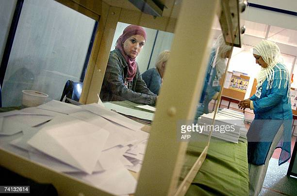 Women are displayed trough a ballot box at a polling station voting for Algerian parliamentary elections 12 May 2007 in the southern town of Lyon...