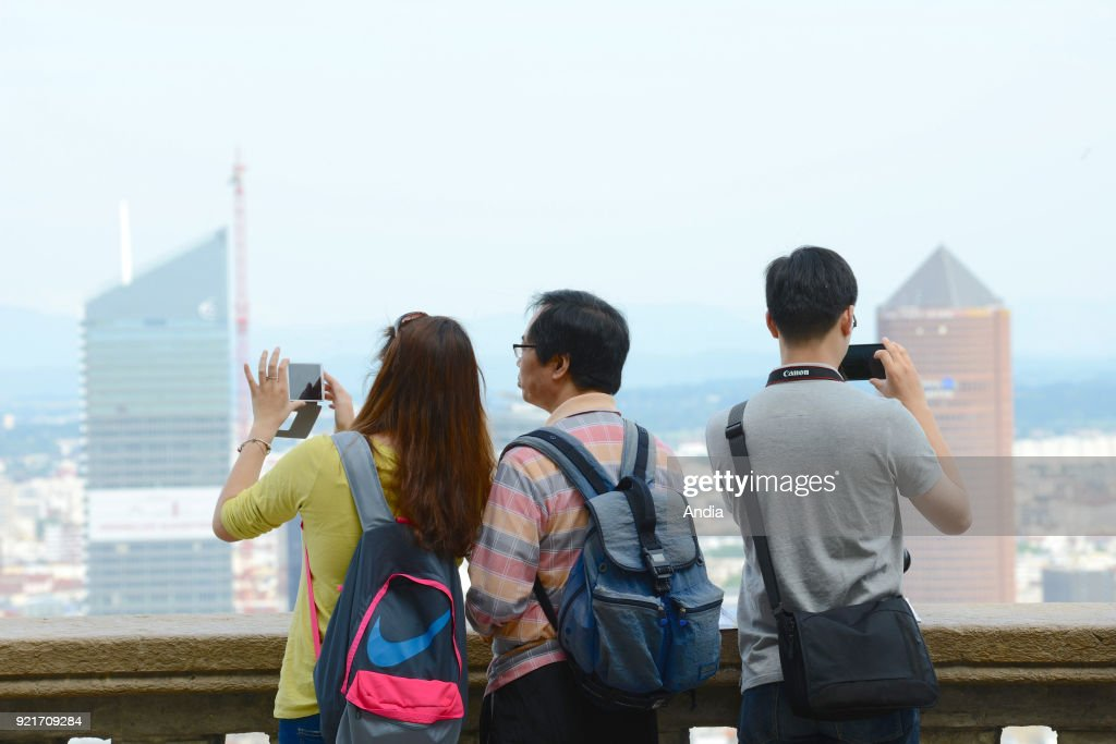 overview of the city from the Basilica of Notre-Dame de Fourviere. Asian tourists taking pictures of the panorama with their smartphones.