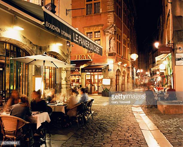lyon, people dining along cobbled street at night - フランス ストックフォトと画像
