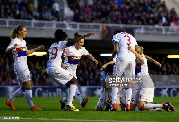 Lyon players celebrate their opening goal during the UEFA Women's Champions League quarterfinal second leg football match between FC Barcelona and...