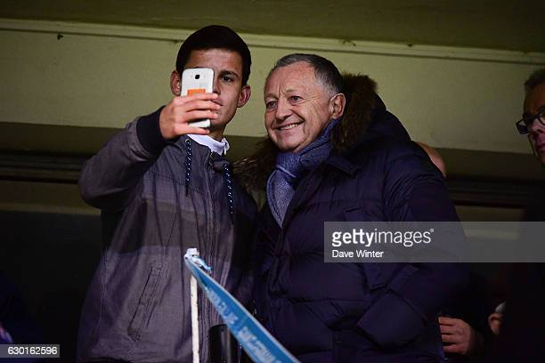 Lyon president Jean Michel Aulas poses for a selfie with a fan during the French Division 1 match between Paris Saint Germain and Lyon at Camp des...