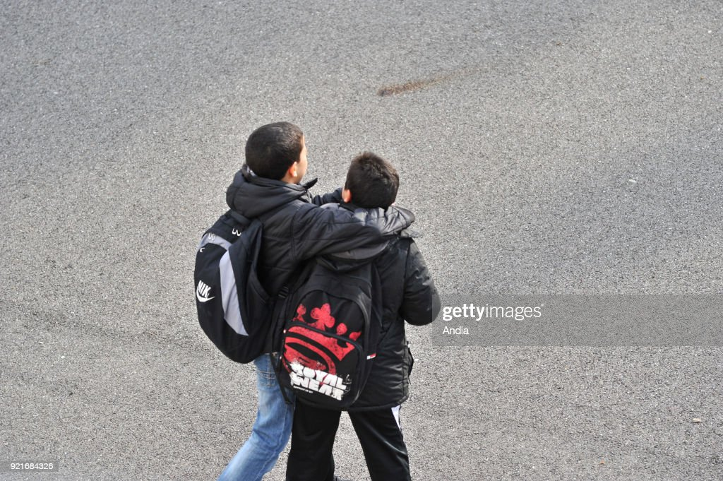 Lyon (south-eastern France). . Public junior high school 'Victor Grignard' in the 8th arrondissement (district). Two secondary-school pupils with backpacks, in the playground, holding each other by the neck.