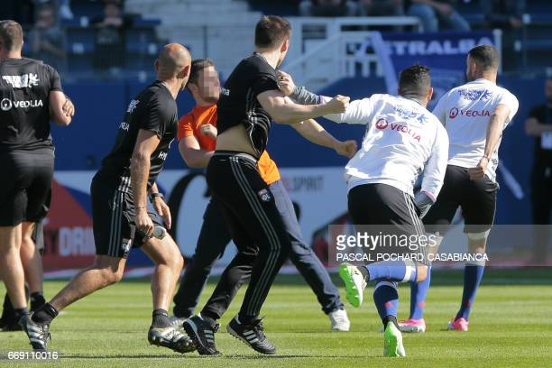 Lyon staff members try to stop a Bastia supporter who invaded the pitch to fight with Lyon players during warm up prior to the French L1 Football...