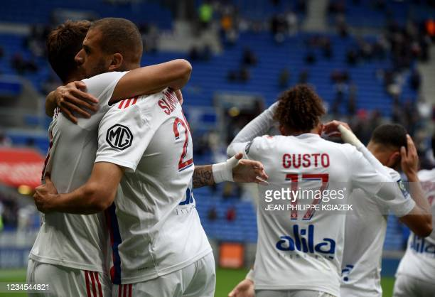 Lyon's Algerian forward Islam Slimani celebrates with teammates after scoring his team's first goal during the French L1 football match between Lyon...