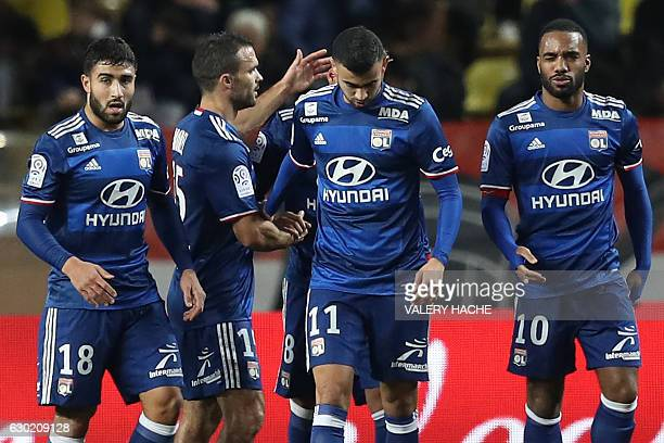 Lyon's Algerian forward Rachid Ghezzal is congratulated by teammates after scoring a goal during the French L1 football match between AS Monaco and...