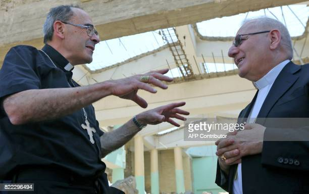 Lyon's Archbishop Cardinal Philippe Barbarin and Louis Raphael Sako the Patriarch of the Chaldean Church in Iraq speak as they walk amid the rubble...