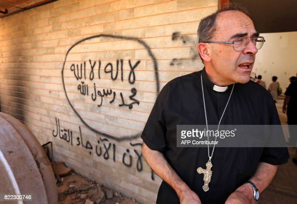 Lyon's Archbishop Cardinal Philippe Barbarin stands next to an Islamic State group graffiti during a visit to the Church of the Annunciation in east...