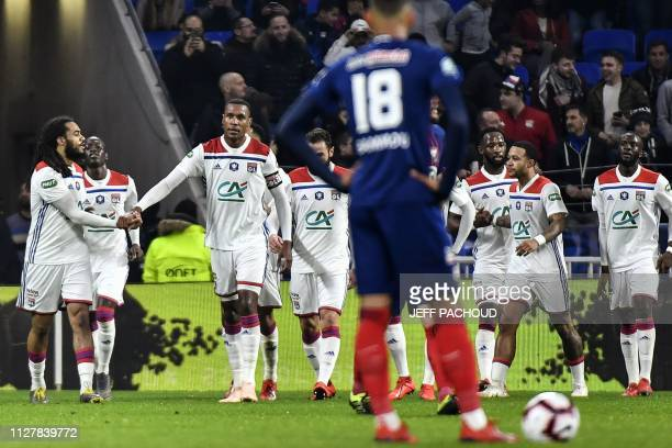 Lyon's Belgian defender Jason Denayer celebrates with teammates after scoring during the French Cup quarter-final football match between Olympique...