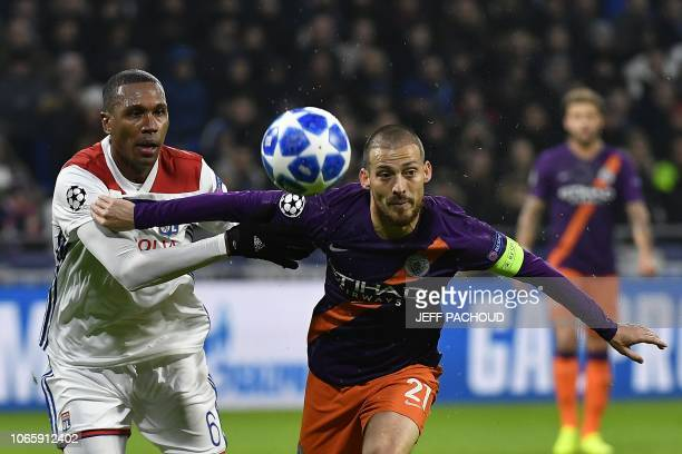 Lyon's Brazilian defender Marcelo vies with Manchester City's Spanish midfielder David Silva as he eyes the ball during the UEFA Champions League...