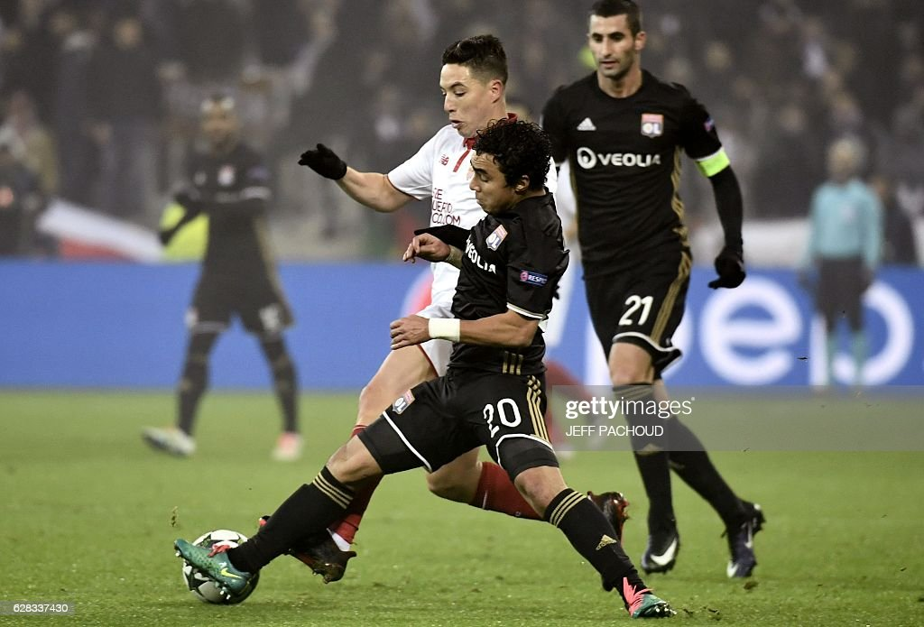 Lyon's Brazilian defender Rafael da Silva (C) vies with Sevilla's French forward Samir Nasri (L) during the UEFA Champions League Group H football match between Olympique Lyonnais (OL) and FC Sevilla at the Parc Olympique Lyonnais in Décines-Charpieu near Lyon, southeastern France, on December 7, 2016. / AFP / JEFF