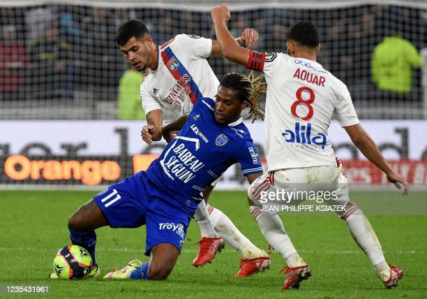 Lyon's Brazilian midfielder Bruno Guimaraes and Lyon's French midfielder Houssem Aouar fights for the ball with Troyes' French forward Gerson Gouveia...