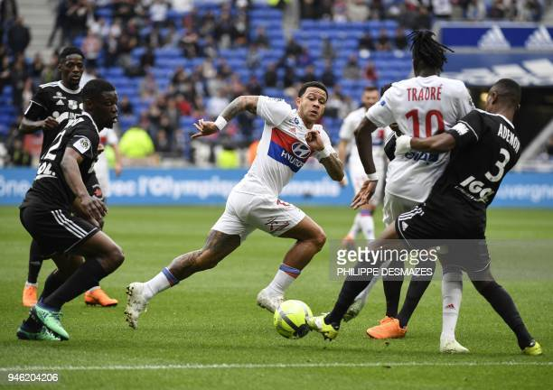 Lyon's Burkinabe forward Bertrand Traore and Lyon's Dutch forward Memphis Depay fight for the ball with Amiens' French midfielder Bakaye Dibassy and...