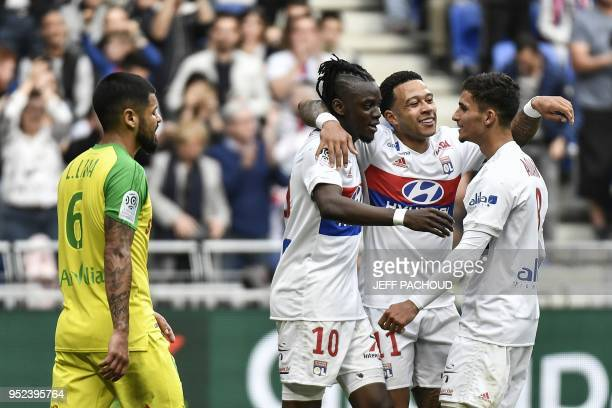 Lyon's Burkinabe forward Bertrand Traore celebrates with his teammates Lyon's Dutch forward Memphis Depay and Lyon's forward Houssem Aouar after...