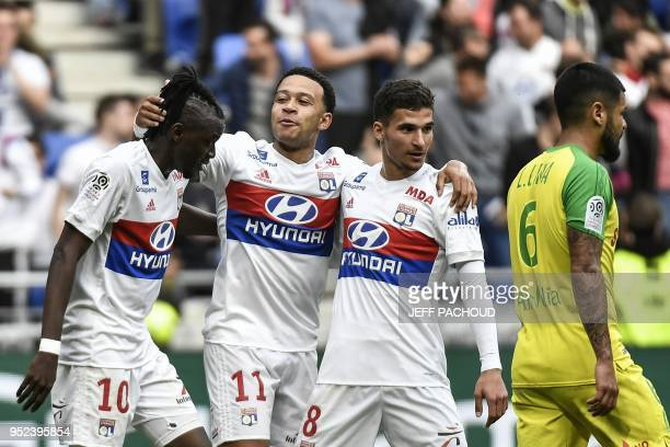 Lyon's Burkinabe forward Bertrand Traore celebrates with his teammates Lyon's Dutch forward Memphis Depay and Lyon's forward Houssem Aouar after...