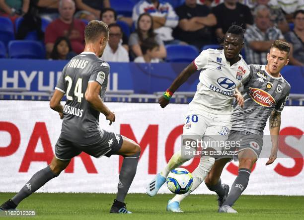 Lyon's Burkinabe forward Bertrand Traore fights for the ball with Angers' French defender Romain Thomas and Angers' French midfielder Pierrick...