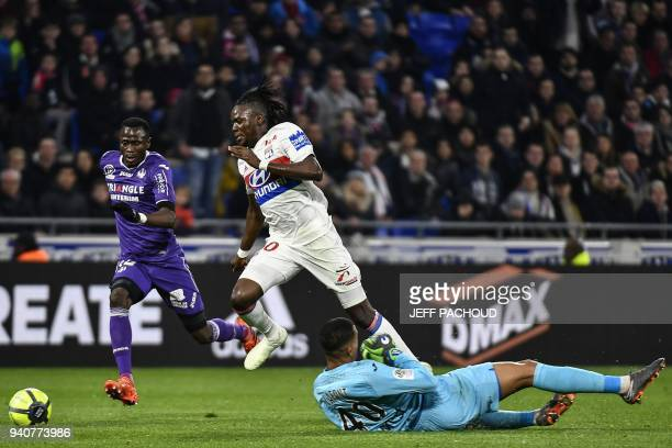 Lyon's Burkinabe forward Bertrand Traore fights for the ball with Toulouse's French goalkeeper Alban Lafont during the French L1 football match...