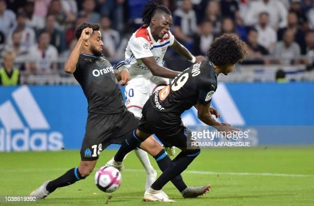 Lyon's Burkinabe forward Bertrand Traore kicks the ball and scores despite Marseille's Brazilian midfielder Luiz Gustavo and French defender Jordan...