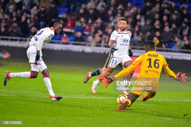 Lyon's Burkinabe forward Bertrand Traore kicks the ball as Reims' French goalkeeper Edouard Mendy dives during the French L1 football match between...