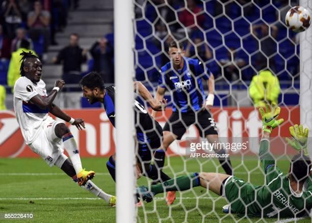 Lyon's Burkinabe forward Bertrand Traore shoots and scores a goal against Atalanta's Albanese goalkeeper Etrit Berisha during the Europa League...