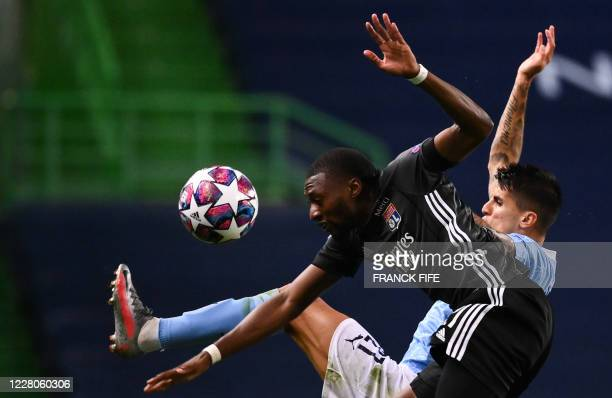 Lyon's Cameroonian forward Karl Toko Ekambi vies with Manchester City's Portuguese defender Joao Cancelo during the UEFA Champions League...