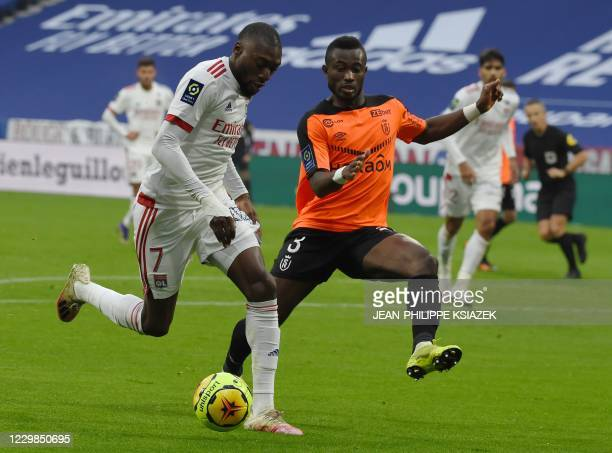 Lyon's Cameroonian forward Toko Ekambi fights for the ball with Reims' Ivorian defender Ghislain Konan during the French L1 football match between...