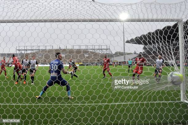 Lyon's defender Mouctar Diakhaby scores a goal as Angers' French goalkeeper Alexandre Letellier looks at the ball during the French L1 football match...