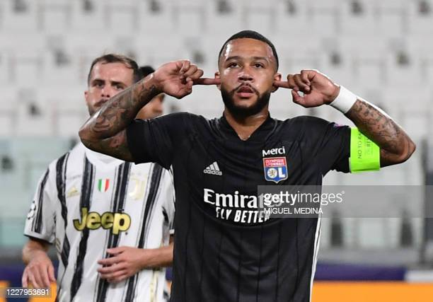 Lyon's Dutch forward Memphis Depay celebrates scoring his team's first goal during the UEFA Champions League round of 16 second leg football match...