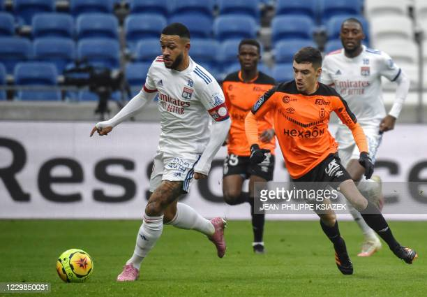 Lyon's Dutch forward Memphis Depay fights for the ball with Reims' French midfielder Mathieu Cafaro during the French L1 football match between Lyon...