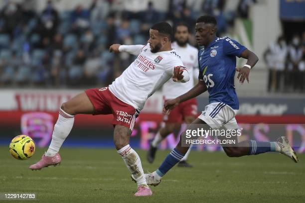 Lyon's Dutch forward Memphis Depay is challenged by Strasbourg's French midfielder Jean-Ricner Bellegarde during the French L1 football match between...