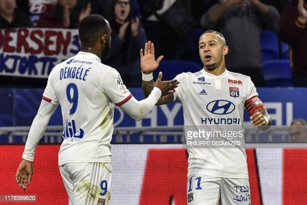 Lyon's Dutch forward Memphis Depay is congratulated by Lyon's French forward Moussa Dembele after scoring during the French L1 football match between...