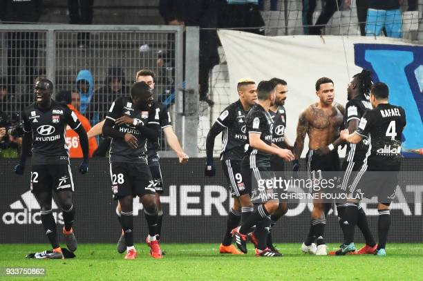 TOPSHOT Lyon's Dutch forward Memphis Depay is congratulated by teammates after scoring a goal during the French L1 football match Marseille vs Lyon...