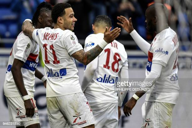 Lyon's Dutch forward Memphis Depay is congratuled by teammates after scoring a goal during the French L1 football match between Olympique Lyonnais...