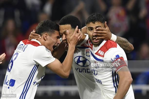 Lyon's Dutch forward Memphis Depay is congratuled by teammates Lyon's forward Houssem Aouar and Lyon's French midfielder Nabil Fekir after scoring...