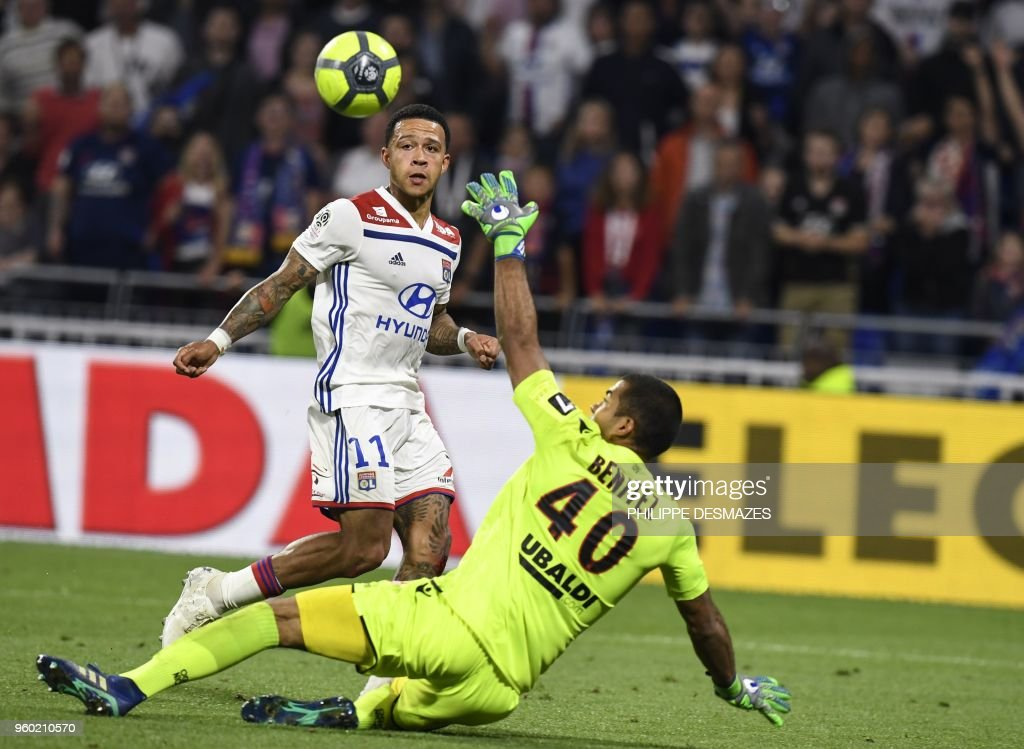 Lyon's Dutch forward Memphis Depay (up) shoots and scores against Nice's Argentinian goalkeeper Walter Benitez (down) during the French L1 football match between Olympique Lyonnais and OGC Nice, on May 19, 2018, at the Groupama Stadium in Decines-Charpieu near Lyon, central-eastern France.