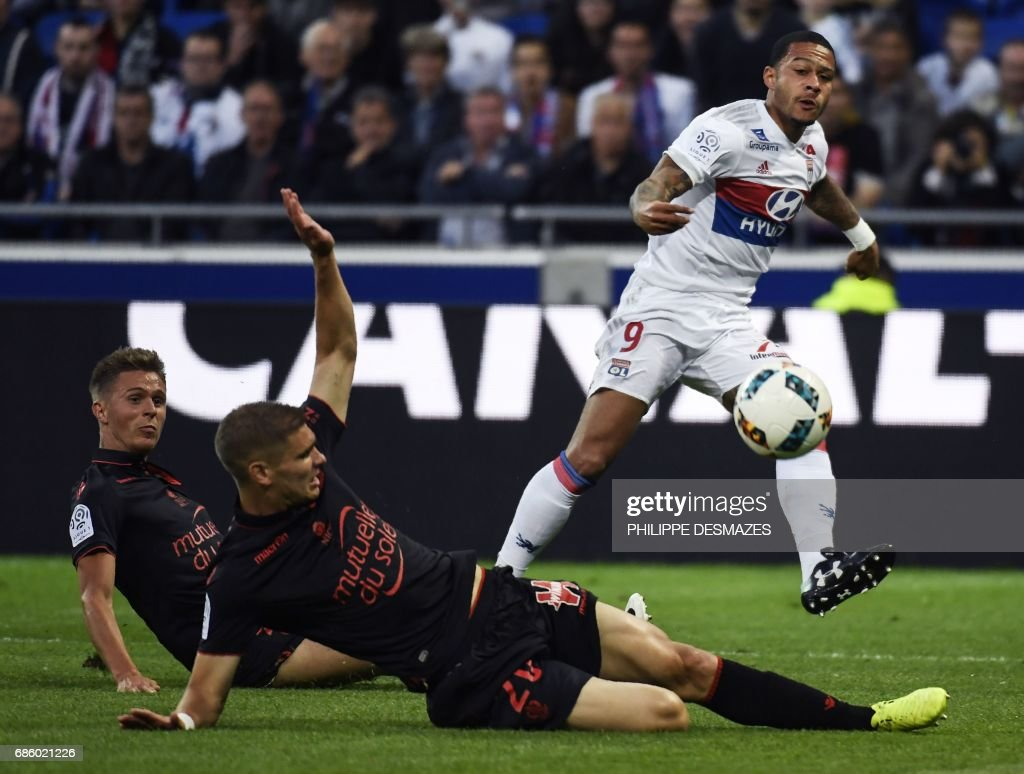 Lyon's Dutch forward Memphis Depay (up) shoots and scores past Nice's French defender Arnaud Souquet (L down) and Nice's French defender Maxime Le Marchand (C) during the French L1 football match between Lyon (OL) and Nice (OGCN) on May 20, 2017, at the Parc Olympique Lyonnais stadium in Decines-Charpieu near Lyon, central-eastern France. /