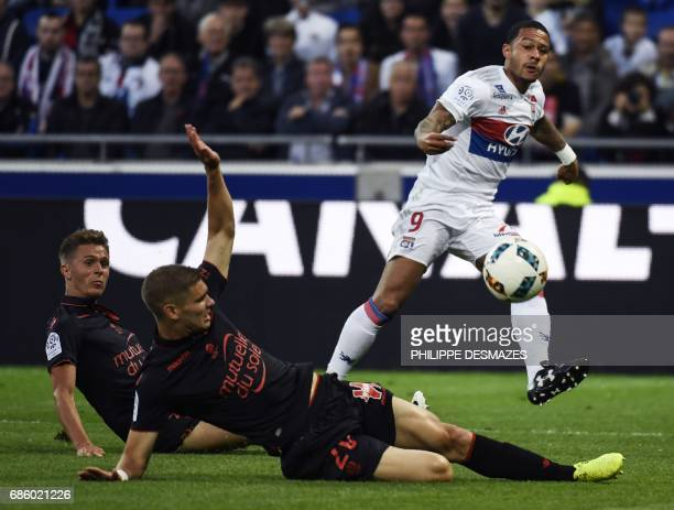 Lyon's Dutch forward Memphis Depay shoots and scores past Nice's French defender Arnaud Souquet and Nice's French defender Maxime Le Marchand during...
