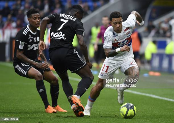 Lyon's Dutch forward Memphis Depay vies with Amiens' French midfileder Harisson Manzala and Amiens' South African midfileder Bongani Zungu during the...