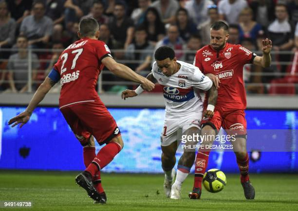 Lyon's Dutch forward Memphis Depay vies with Dijon's French midfielder Jordan Marie and Dijon's French defender Cedric Varrault during the French L1...