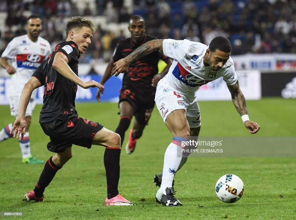 Lyon's Dutch forward Memphis Depay (R) vies with Nice's French defender Arnaud Souquet (L) during the French L1 football match between Lyon (OL) and Nice (OGCN) on May 20, 2017, at the Parc Olympique Lyonnais stadium in Decines-Charpieu near Lyon, central-eastern France. /