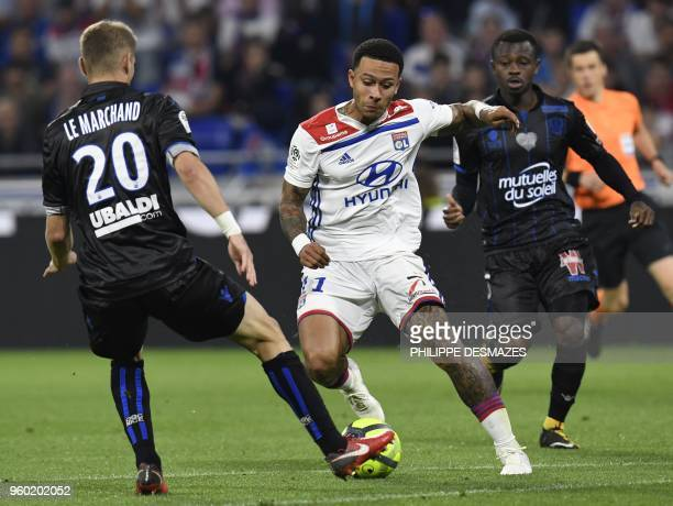 Lyon's Dutch forward Memphis Depay vies with Nice's Ivorian midfielder Jean Michael Seri and Nice's French defender Maxime Le Marchand during the...