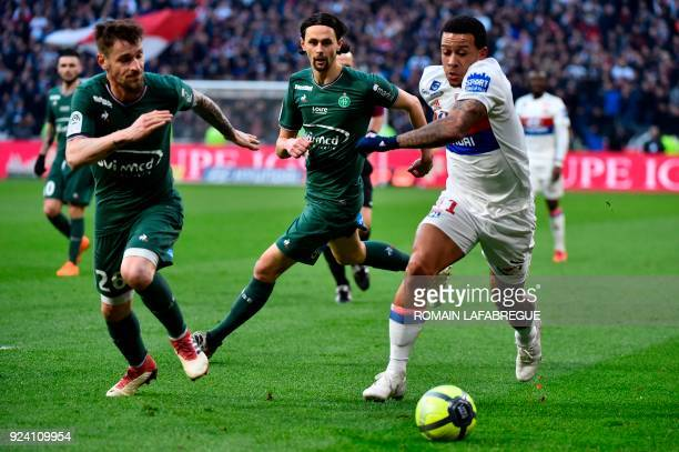 Lyon's Dutch forward Memphis Depay vies with SaintEtienne's French defender Mathieu Debuchy and SaintEtienne's Serbian defender Neven Subotic during...