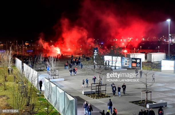 Lyon's fans use red flares before before the Europa League football match Olympique Lyonnais vs CSKA Moscow on March 15 at the Groupama Stadium in...