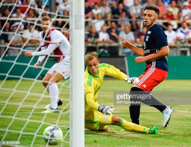 Lyon's forward Amine Gouiri scores his team's second goal past Ajax goalkeeper Stan van Bladeren during a friendly football match between Olympique...