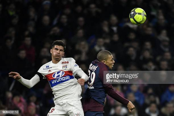 Lyon's forward Houssem Aouar heads the ball with Paris SaintGermain's French forward Kylian Mbappe during the French L1 football match between...